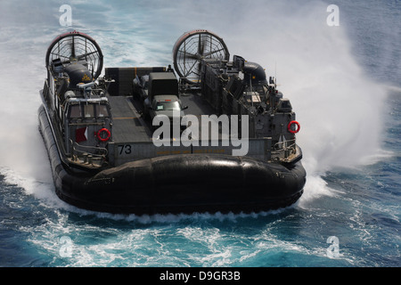 A Landing Craft Air Cushion prepares to enter the well deck of USS Essex. - Stock Photo