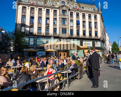 Bar cafe in Oslo, Norway, Scandinavia, Europe in the early evening with people sitting outside in the sun - Stock Photo