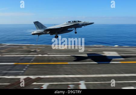 An F/A-18F Super Hornet flies over the flight deck of USS George H.W. Bush. - Stock Photo