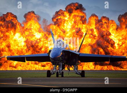 A wall of fire erupts behind a U.S. Navy F/A-18 Hornet aircraft. Stock Photo