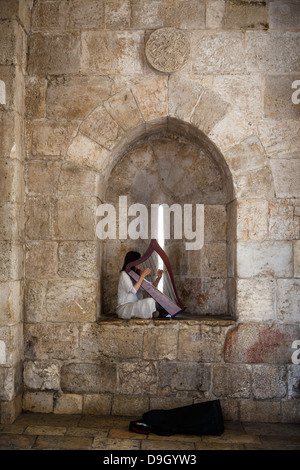 Woman playing the harp at Jaffa gate in the old city, Jerusalem, Israel. - Stock Photo