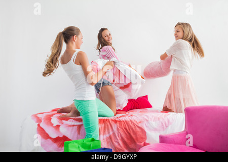 Girls having pillow fight on the bed at a slumber party - Stock Photo
