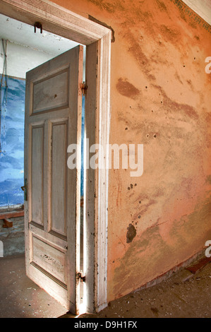 Open door to a room full of sand in Kolmanskop, a ghost mining town in Namibia, Africa. The desert has reclaimed - Stock Photo