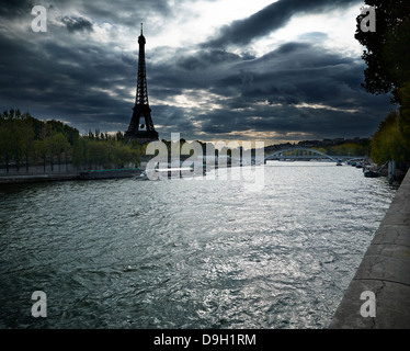 Eiffel Tower on a stormy day from across the Seine - Stock Photo