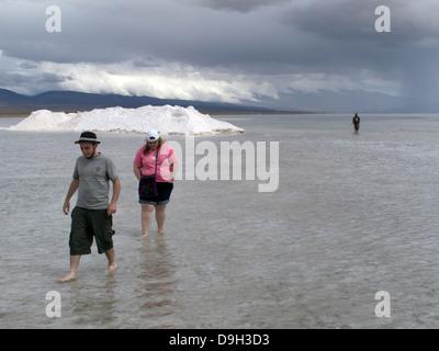 Salinas Grandes. Three tourists walking barefoot in stagnant rain water on the salt crust - Stock Photo
