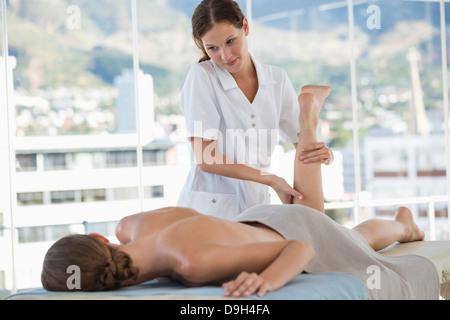 Woman receiving leg massage from a massage therapist - Stock Photo