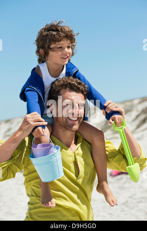 Man carrying his son on shoulders on the beach - Stock Photo