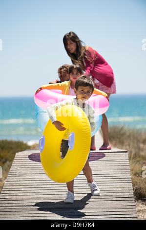 Woman with her children holding inflatable rings on a boardwalk on the beach - Stock Photo