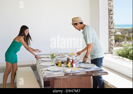 Couple arranging food on a dining table - Stock Photo