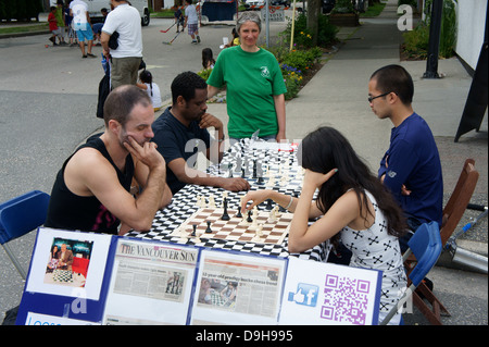 Young woman chess champion and people of different races playing chess outdoors on Main Street in Vancouver, BC, - Stock Photo