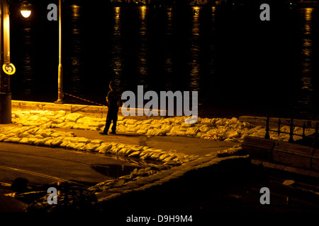 Police officer patrolling the street surrounded by sandbags on the flooded banks of the River Danube, Budapest, - Stock Photo
