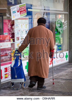aged back bag behind cane disabled one pedestrian person rear senior shopping single stick street trolley urban - Stock Photo