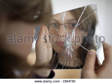Teenage girl holding a broken hand mirror - Stock Photo