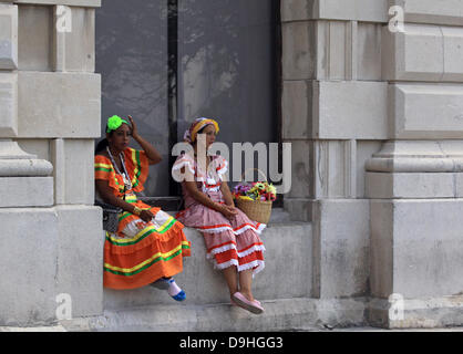 Two young women with flowers and wearing colourful traditional Cuban dresses await paying tourists to take photo - Stock Photo
