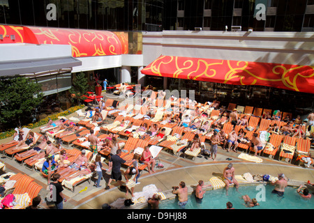 Nevada Las Vegas Downtown Golden Nugget Hotel & Casino hotel swimming pool lounge chairs guests sunbathing - Stock Photo