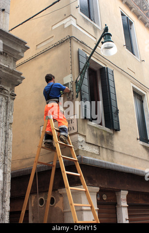 Venetian workman repairing the street lamps of Venice. - Stock Photo