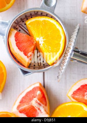 Fresh citrus fruits with traditional manual juicer on a wooden table. - Stock Photo