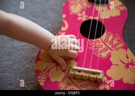 Baby's hand on pink Ukulele - Stock Photo