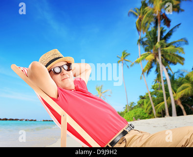 Mature male tourist enjoying on a tropical beach next to a sea and palms - Stock Photo