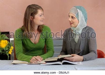 Muslim woman teaching Quran to her friend - Stock Photo