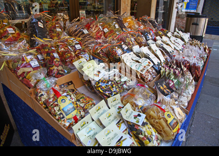 Lots of different sorts of coloured spaghetti for sale in bags on a market stall outside a shop Venice Italy - Stock Photo