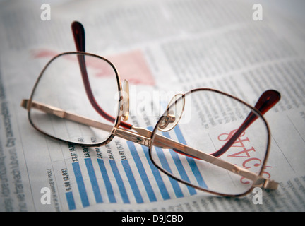 Glasses on a newspaper with financial chart - Stock Photo