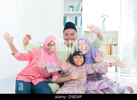 Happy Asian family at home. Muslim family having fun. Southeast Asian parents and children open arms smiling. - Stock Photo