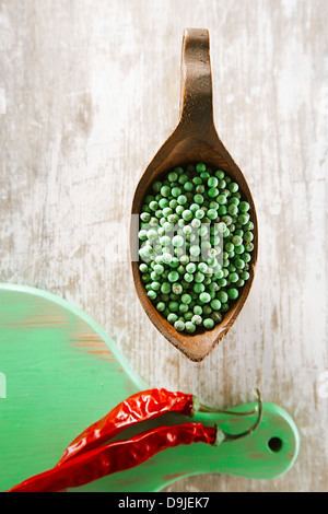 green peppercorn in bowl and red chillies on green wooden board, shallow dof - Stock Photo