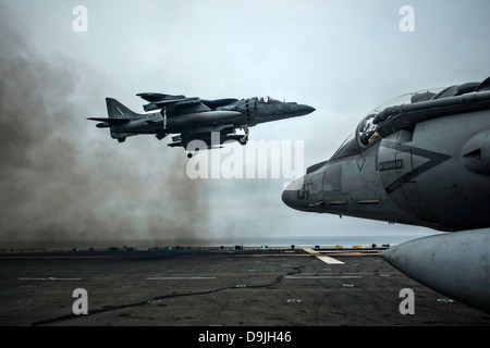 A US Marine Corp A/V-8B Harrier fighter jet performs a vertical take off on the flight deck of the amphibious assault - Stock Photo