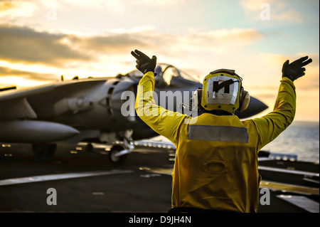 A US Navy deck crew directs a Marine Corp AV-8B Harrier fighter jet before take off on the flight deck of the amphibious - Stock Photo