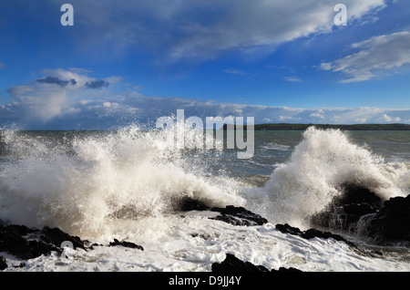 Waves and rocks near Ballinacourty Lighthouse at the entrance to Dungarvan Bay, County Waterford, Ireland - Stock Photo