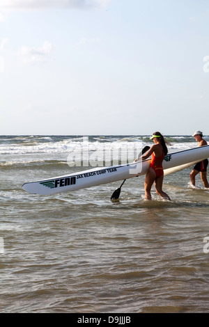 Young man and woman competing in the 4th Annual JAX Beach Paddling Challenge. - Stock Photo