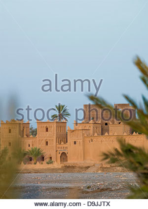 A kasbah sits on the banks of a dried up river in the Skoura Oasis in Morocco - Stock Photo