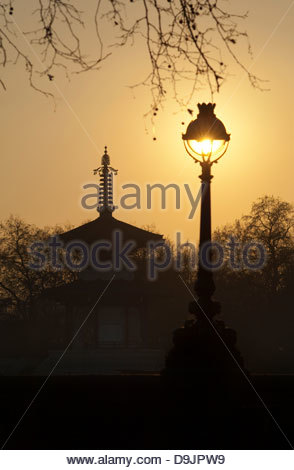 An old bandstand and street light silhouetted again a low sun in London, UK - Stock Photo