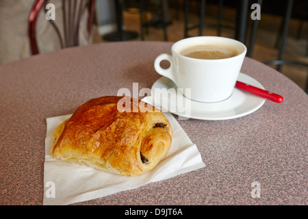 pain au chocolate and cafe au lait in a cafe bar in france - Stock Photo