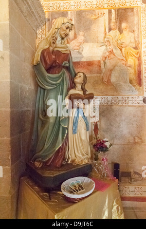A statue in the church of Sant' Anna, Specchia Gallone, near Lecce, Puglia, Italy. Frescoes tell the story on every - Stock Photo