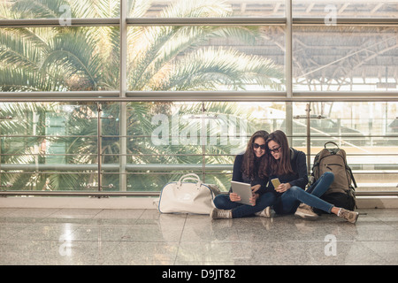 Teenage girls sitting on floor using digital tablet Stock Photo