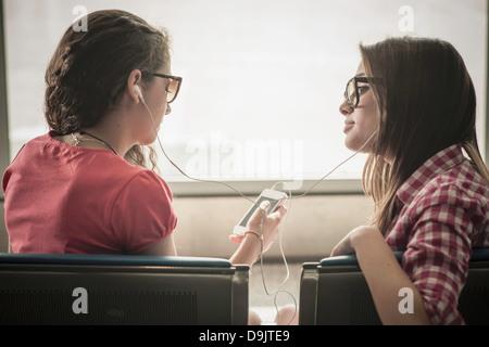 Two teenage girls wearing sunglasses listening to music - Stock Photo