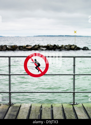 No swimming sign on pier railing - Stock Photo