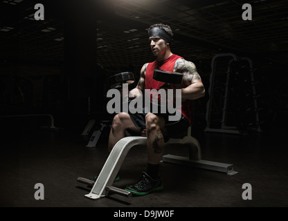 Muscular young man holding dumbbells in gym - Stock Photo