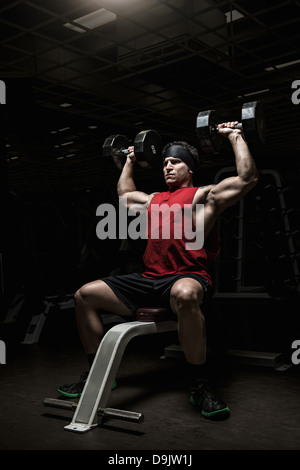 Muscular young man performing shoulder raises with dumbbells in gym - Stock Photo
