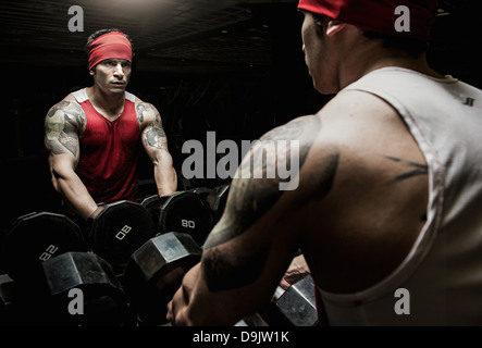 Muscular young man looking in gym mirror - Stock Photo