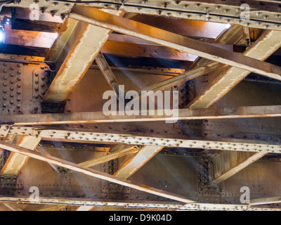 Shafts of light below railway tracks on a bridge in Amsterdam, Netherlands. - Stock Photo