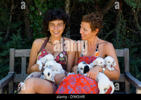 two young girl with a dog puppies of the English Setter breed - Stock Photo
