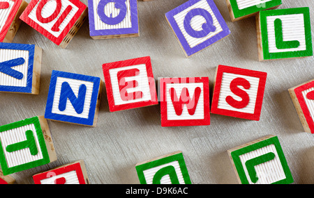 Wooden blocks forming the word NEWS in the center - Stock Photo