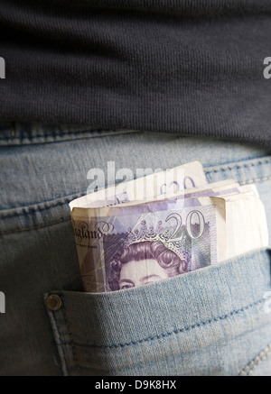 Roll of twenty pound notes in back pocket of denim jeans - Stock Photo