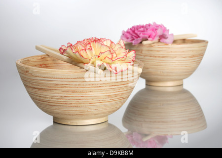 Wooden bowls with rod and carnation blossoms - Stock Photo