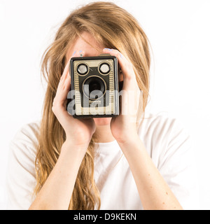 A young woman with long blonde hair holding using an old Kodak Box Brownie camera - Stock Photo