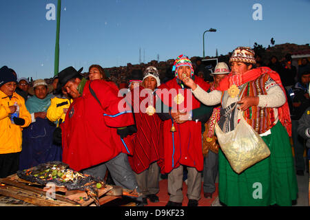 LA PAZ, BOLIVIA, 21st June. A female Aymara amauta or spiritual leader throws offerings of coca leaves onto an unstarted - Stock Photo