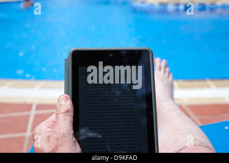 man reading ebook on tablet computer by the side of a swimming pool on holiday salou costa daurada spain - Stock Photo
